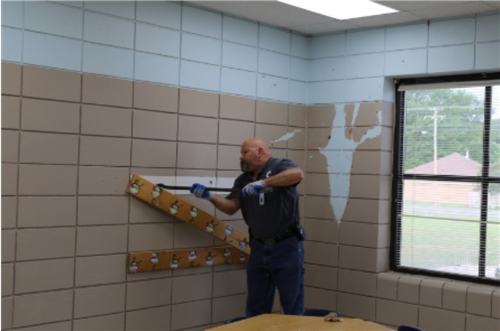 Maintenance Worker prying coat rack off wall during remodel of elementary school