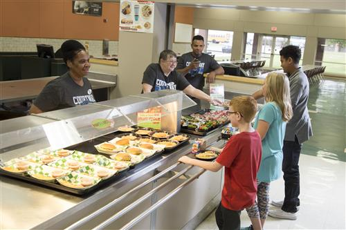 School Cafeteria workers greeting three middle school students as they get their lunch trays and come through the lunch line.
