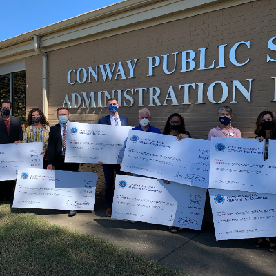 State Reps Steve Magie and Stephen Meeks present checks to administrators from Conway Schools